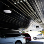 Commercial building with real wood siding, custom painted black flat panels and black ribbed cladding on parking garage ceiling