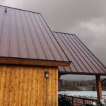 Burgundy toned rustic red hidden fastener roofing panel on a cedar building in Kenora Ontario