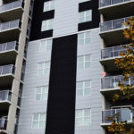 black corrugated steel cladding paired with regent grey hidden fastener panels on multi-storey apartment building