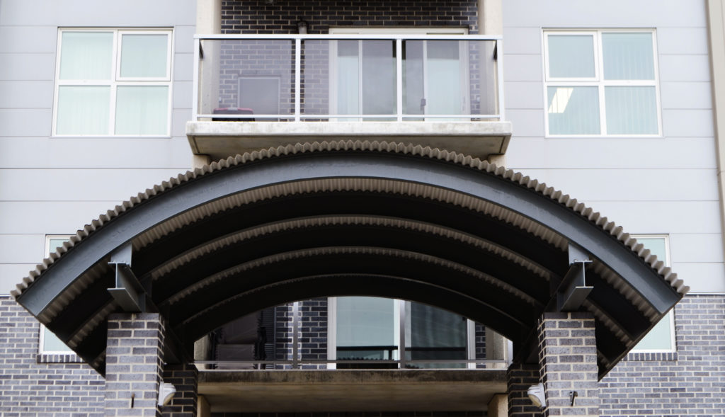 black corrugated metal cladding on curved steel beams at apartment entrance